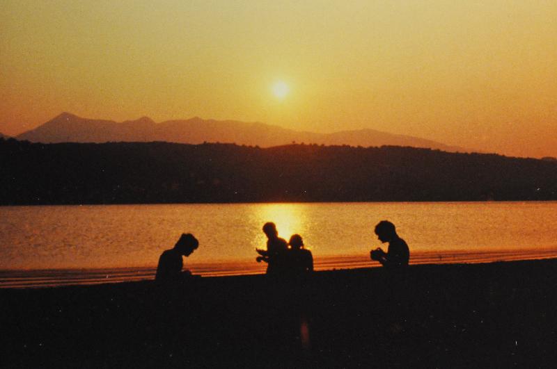 Vier Silhouetten vor einem See, im Hintergrund die Sonne.