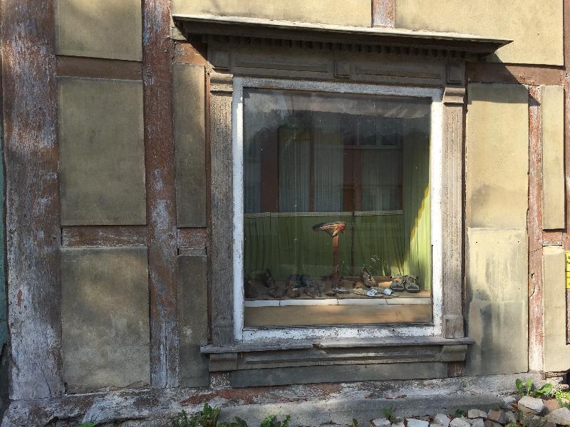 Ein altes Fachwerkgebäude mit Schaufenster, in der Auslage Schuhe