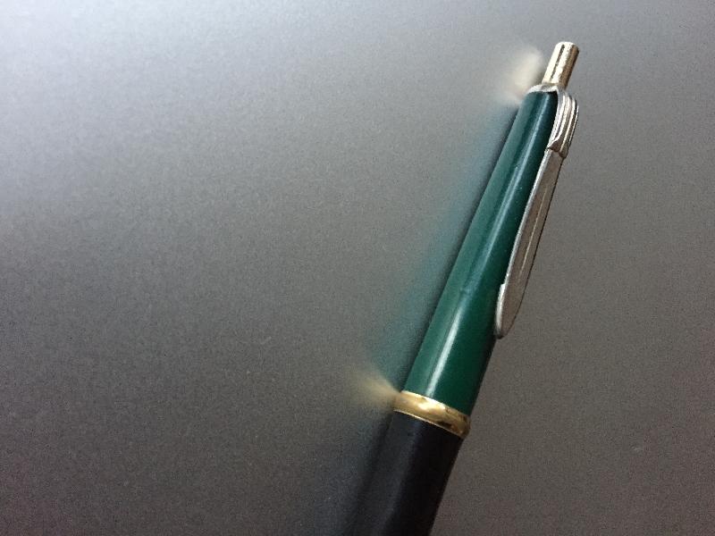 Ein Kugelschreiber liegt auf einer etwas reflektierenden Unterlage