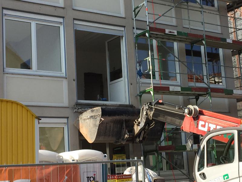 Eine geöffnete Balkontür, statt einem Balkon eine Baggerschaufel