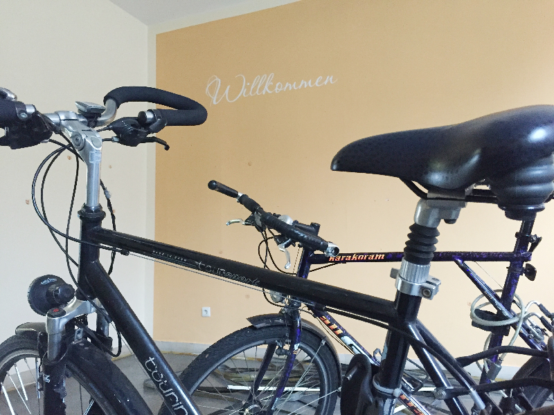 Zwei Fahrräder, an einer Wand ist das Wort Willkommen zu lesen